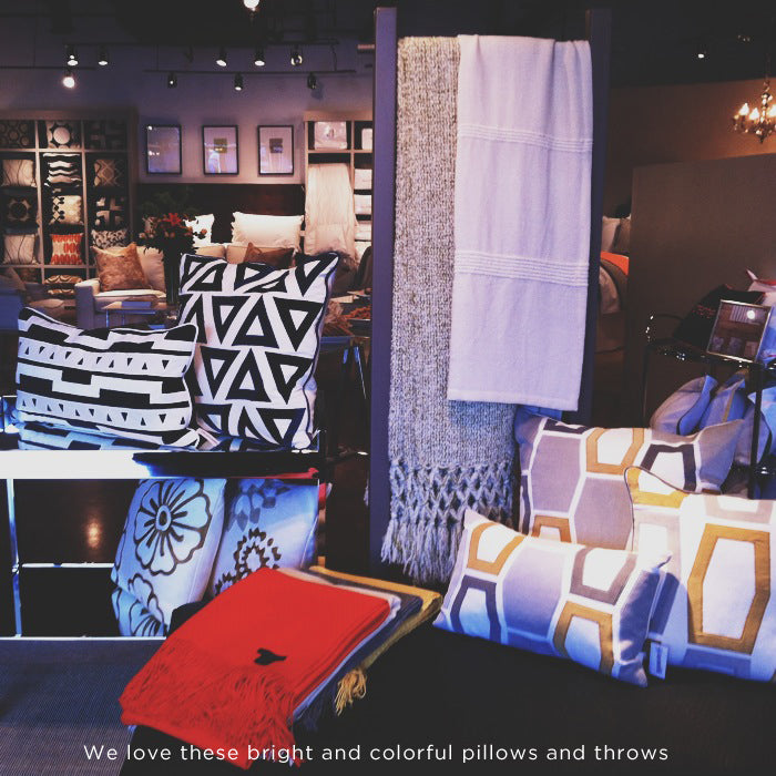 A store display with a variety of decoritive pillows in bold, modern prints