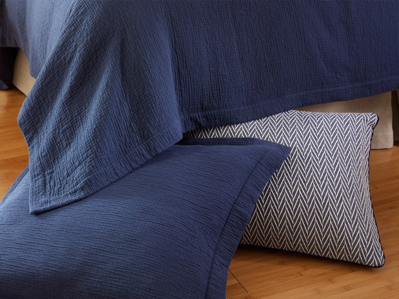 Textured matelassé coverlet and sham in navy with a chevron accent pillow