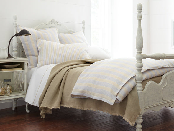 Country style luxury bed with subtly striped duvet cover and shams