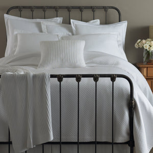 White diamond matelasse coverlet and shams on an all white bed