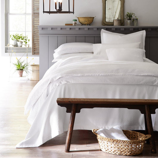 Modern seersucker inspired white duvet cover and shams on an all white bed