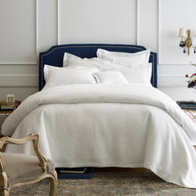 Load image into Gallery viewer, Stone washed matelasse coverlet and shams on an all white bed with navy headboard