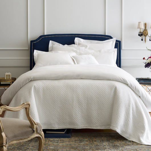 Stone washed matelasse coverlet and shams on an all white bed with navy headboard