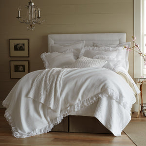 White ruffled duvet cover and shams on an all white bed