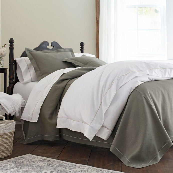 Neutral linen bedding with contrasting satin stitch