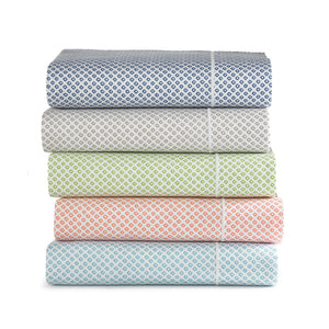 Stack of geometric patterned printed sateen sheets in red, green, coral, linen, blue, aqua