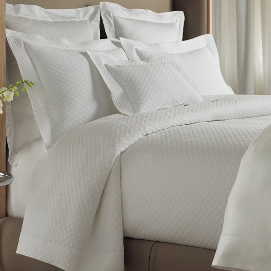 Tailored bed with diamond pattern quilted matelasse coverlet and shams