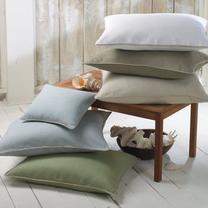Stack of linen corded throw pillows and decorative pillows in various colors