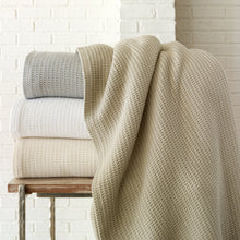 Load image into Gallery viewer, Waffle style cotton blanket stack on side table in pearl, linen, flint, and white