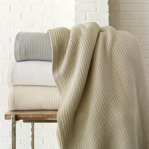 Waffle style cotton blanket stack on side table in pearl, linen, flint, and white