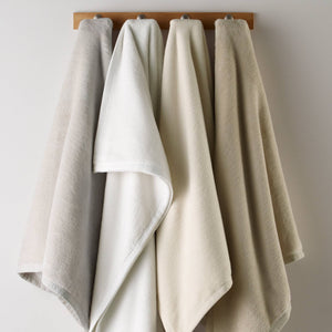 Neutral color blankets hanging on a rack
