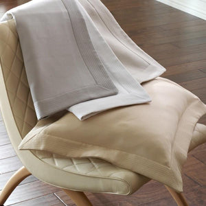 Angelina matelasse pique shams draped over a chair