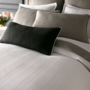 white bedding with gray and black pillows