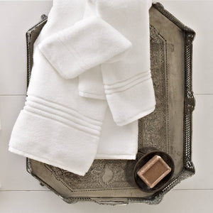 white cotton bath towels on a bathroom tray