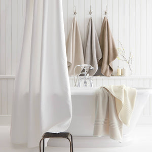 bright white bathroom with neutral color towels