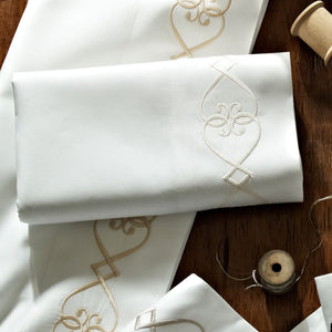 Embroidered white sateen flat sheet with spools of thread