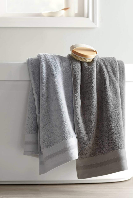 gray bath towels draped over bathtub