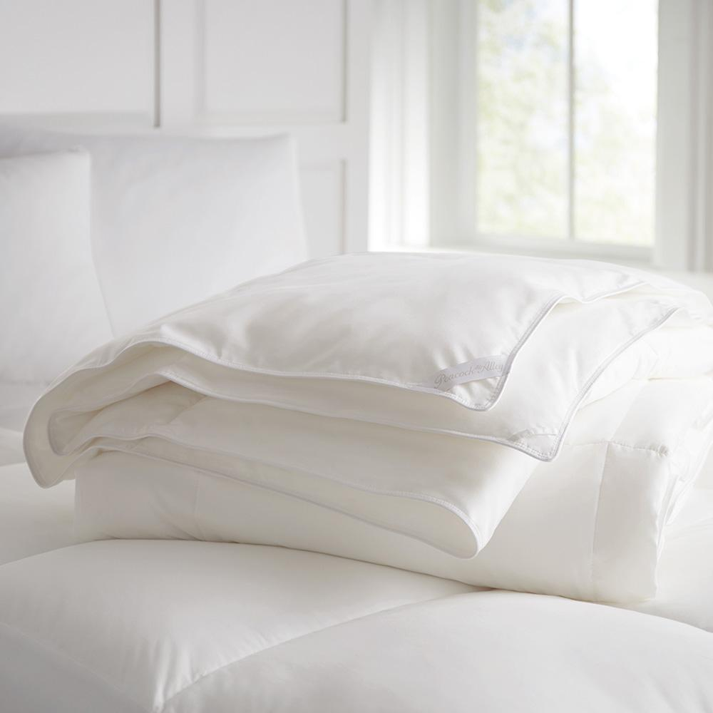 White goose down duvet folded laying on a bed with mattress enhancer