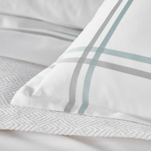 detail photo of corner of striped pillow sham in sage