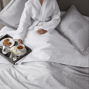 elise jacquard sham woman in bathrobe eating breakfast in bed
