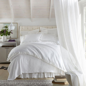 all white ruffled bedding in a light bedroom