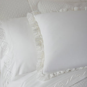 white bedding with ruffled pillow shams