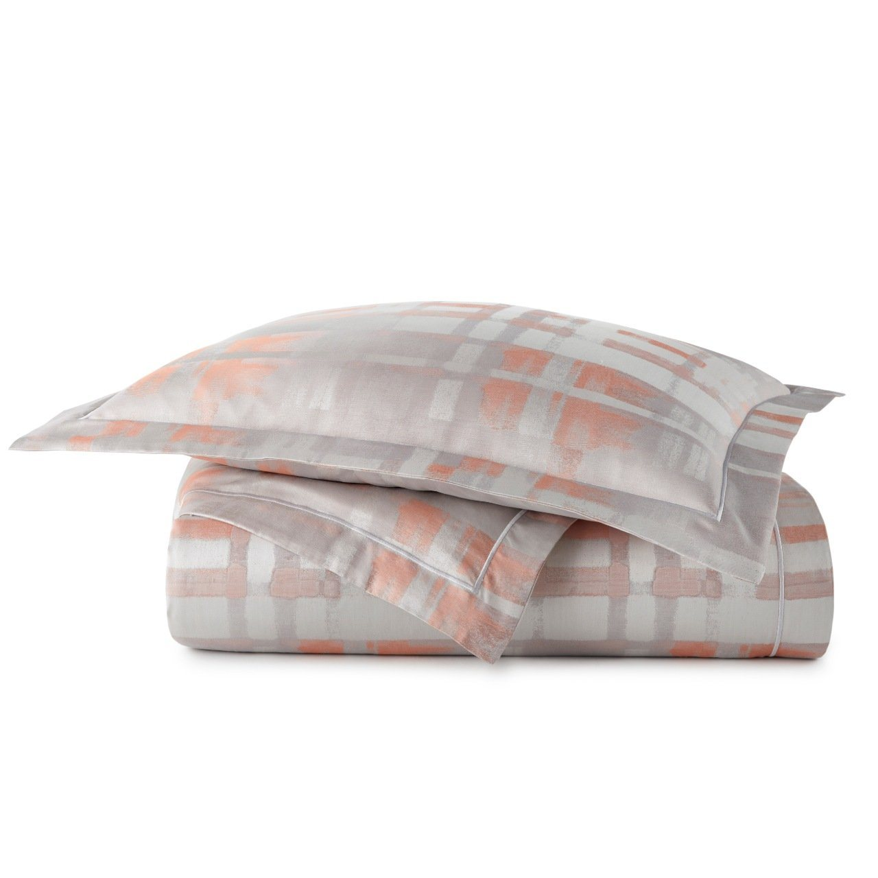 stack of Enzo duvet cover and sham in coral