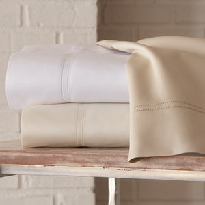 messy stack of lyric percale sheets in neutral colors