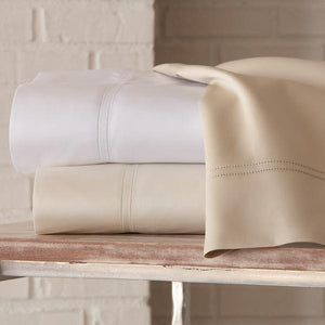 messy stack of virtuoso sateen sheets in neutral colors