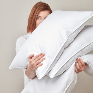 woman holding white goose down bed pillow inserts