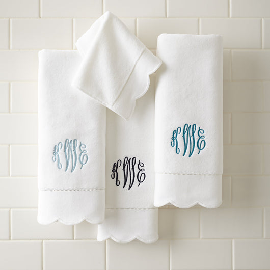 Flat lay of monogrammed scalloped cotton hand towels