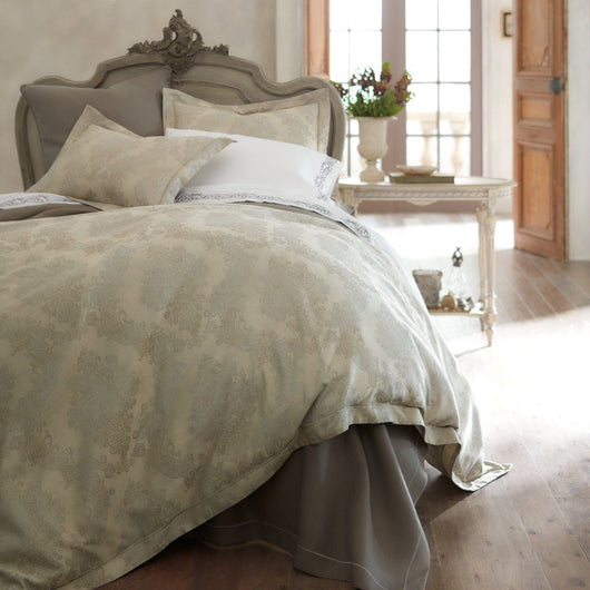 Italian jacquard duvet cover and shams on a formal bed with hues of champagne and grey