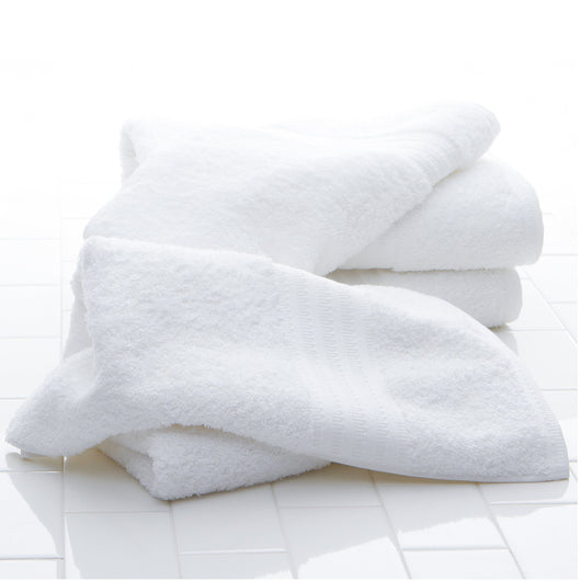 White cotton bath towels laying on a white tile floor