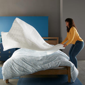 woman putting white 4 square quilted coverlet on bed