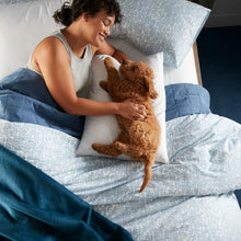 Load image into Gallery viewer, woman and dog on bed with denim blue Fern duvet cover