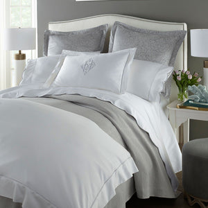 white and gray bedding with scalloped sheets and pillow cases