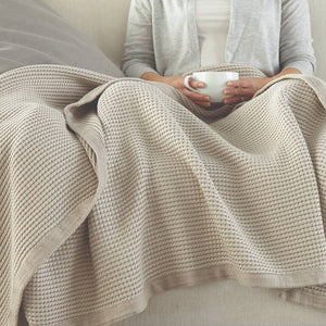 Woman sitting covered up with a blanket