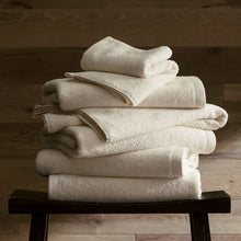 Load image into Gallery viewer, stack of white cotton bath towels on a stool