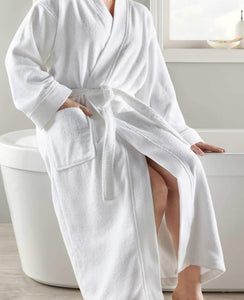 woman in white plush cotton robe sitting on bathtub