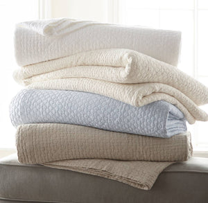 messy stack of neutral color coverlets peacock alley