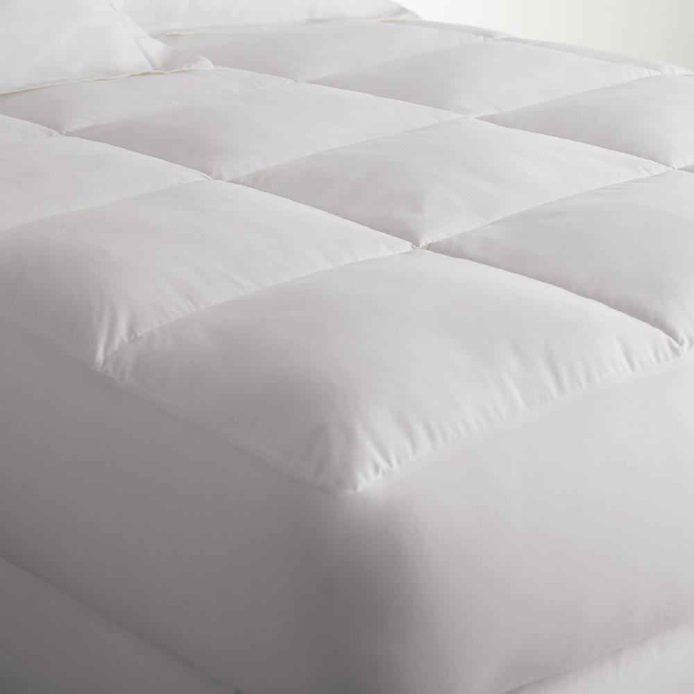 Down alternative mattress enhancer and mattress cushion on a bed