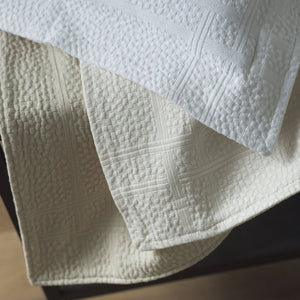 Detail of a pebble pattern matelasse sham with engineered border in white, ivory, and linen colors