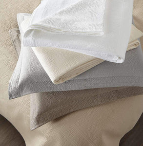 messy stack of folded Montauk shams coverlets in various colors