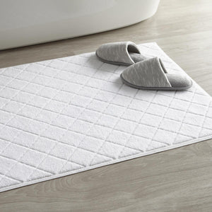 White slippers on top of lattice bath rug
