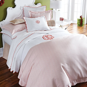 Monogrammed bed with red dotted geometric patterned sateen duvet cover
