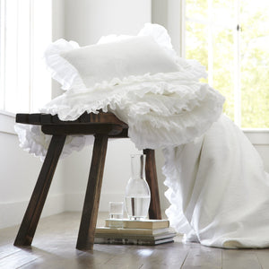 White cotton ruffled sham and duvet cover laying over a brown stool