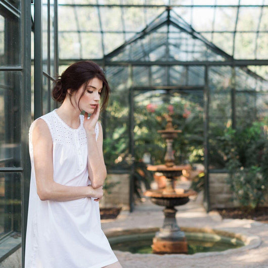 Brown hair woman wearing a white luxury cotton nightgown / sleepwear in a garden
