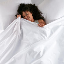 Load image into Gallery viewer, woman laying in bed with 40 winks percale sheets