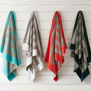 Soleil Striped Beach Towel various colors hanging on wall