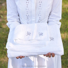 Load image into Gallery viewer, Woman holding stack of folded Grange white bath towels